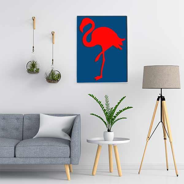 Cadre en métal flamant rose en bleu et fond rouge dans salon