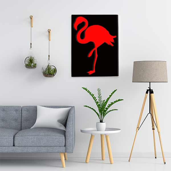 Cadre en métal flamant rose en noir et fond rouge dans salon