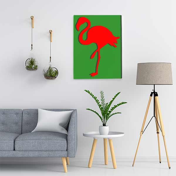 Cadre en métal flamant rose en vert et fond rouge dans salon